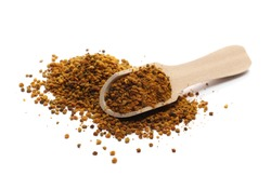 Pollen pile with wooden spoon, isolated on white background
