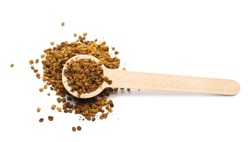 Pollen pile with wooden spoon isolated on white background