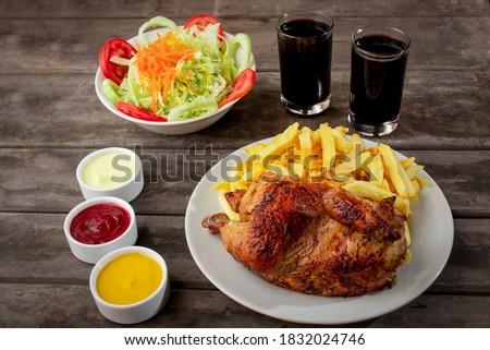 Pollo a la brasa con papas fritas y ensalda en  una mesa de madera Foto d'archivio ©