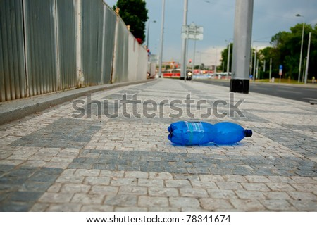 Polluted city series. Wasted PET bottle on sidewalk. Soft focus image, focus on the bottle.