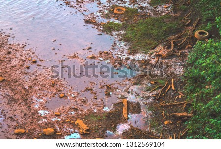 Pollution Along a River Bank in the Form of Oil, Tires, and Coal Mine Drainage.