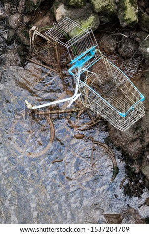Pollution by dumped bicycles and a shopping cart at the edge of a river in the Netherlands #1537204709