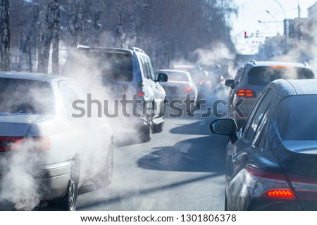 pollution from the exhaust of cars in the city in the winter. Smoke from cars on a cold winter day stock photo
