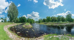 Poltsamaa river, one of the most interesting rivers in Estonia flowing through wild areas. White clouds, blue sky and trees reflecting in water. Sunny summer day in Estonia, Europe.