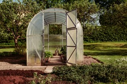Polycarbonate greenhouse in the garden for growing your own fresh food with doors open and a watering can in the centre in late afternoon light. Compact DIY solution for gardens.