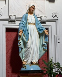 polychrome sculpture of the immaculate virgin with a crown of stars crushing the serpent with her feet over the ball of the world