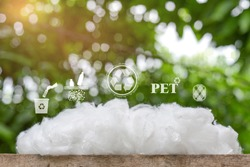 Polyester stable fiber on wooden plank with green background,recycle icon,picking up Plastic Bottle,PET icon&Yarn icon.Chemical concept