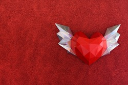 Polygonal heart with wings on a soft fleecy red background. Congratulations on Valentine's Day. mock up and copy space.