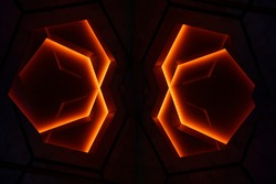 Polygonal lighting elements of suspended ceiling. Abstract architecture and modern interior background. Hexagonal lamps glowing in darkness. Minimal design. Decorative energy flow.