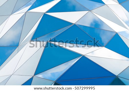 Polygonal triangle glass facade of modern building. Cloudy sky reflects in glass