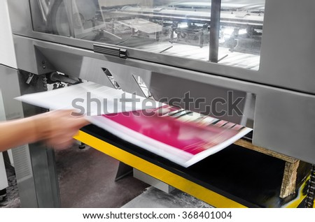 polygraphic process in a modern printing house, print operator pulls printed sheet of paper #368401004