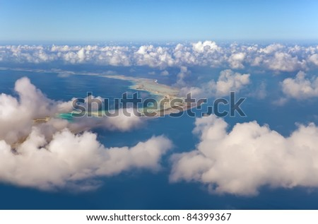 Polynesia. The atoll ring at ocean is visible through clouds. Aerial view