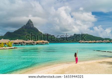 Polynesian hula dancer dancing on Bora Bora beach at luxury overwater bungalows hotel resort at luau show party for tourists. Tahiti, French Polynesia.