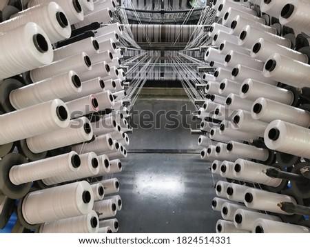 polypropylene plastic flat yarn bobbins loaded on circular loom weaving machine to produce woven fabric  Photo stock ©