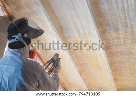 Polyurea Spraying, warming foam coating of roof, worker during insulation process, selective focus on wall