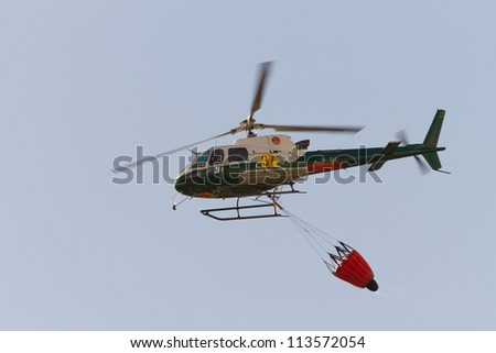 POMBAL, PORTUGAL - SEPTEMBER 22: Fire rescue helicopter, with water bucket, after water drop on Wildfire, in Pombal, Portugal on September 22, 2012