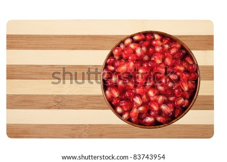 Pomegranate fruits in a wooden bowl on a bamboo board