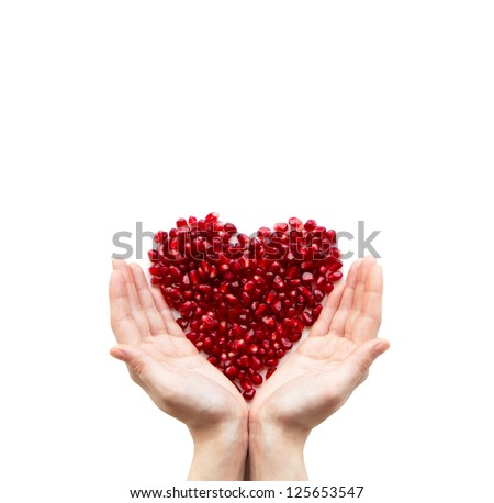 Pomegranate heart in hands on a white background - stock photo