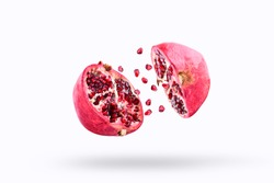 Pomegranate in flight burst on a white background, isolated. Cut half pomegranate flying in the air. Pomegranate fruit explosion