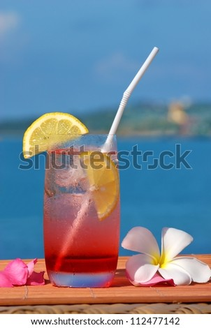 Pomegranate juice and the background sea. Decorated with frangipani flowers and citrus fruits.