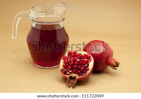 Pomegranate juice in a jug and ripe pomegranate