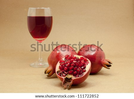 Pomegranate juice in a wine glass and ripe pomegranate