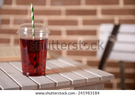 Pomegranate juice in fast food closed cup with tube and book on wooden table and brick wall background