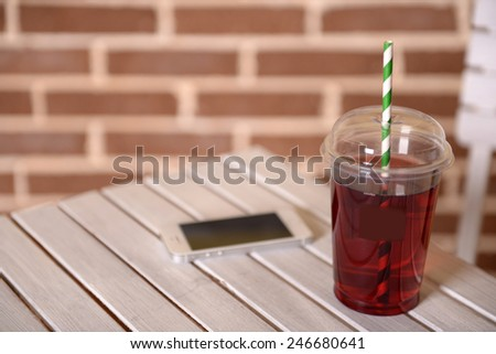Pomegranate juice in fast food closed cup with tube and mobile phone on wooden table and brick wall background