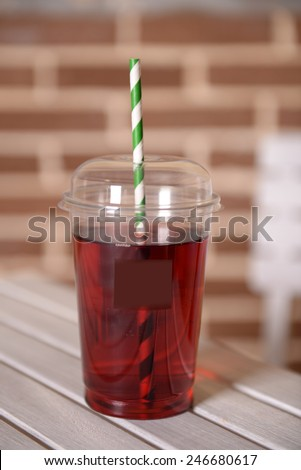 Pomegranate juice in fast food closed cup with tube on wooden table and brick wall background