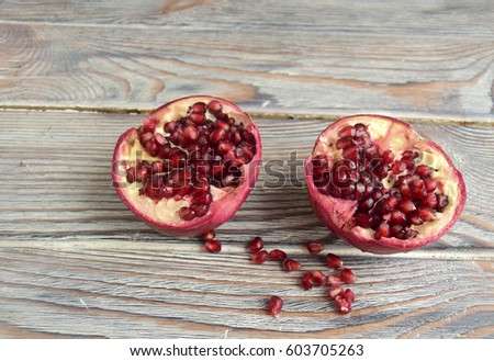 Pomegranate lie on a wooden table. Grains red, juicy, fresh #603705263