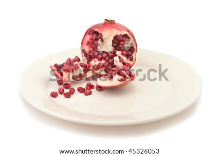 Pomegranate on a plate, isolated over white