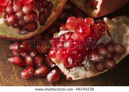 Pomegranate on wooden surface broken open with seeds scattered