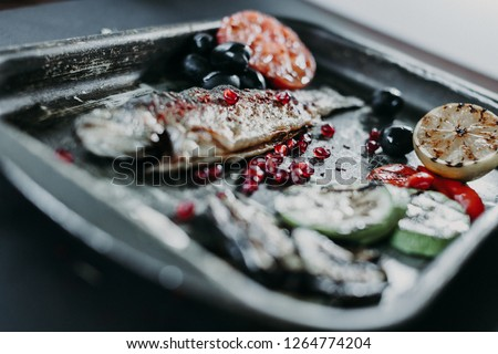 Pomegranate seeds on the grill fried trout fish and on the steel metal tray with a fried lemon, fried tomato and zucchini near by. Shallow focus on the pomegranate seeds. #1264774204