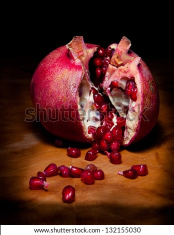Pomegranate: Studio still life shot of a pomegranate broken open to reveal the seeds.