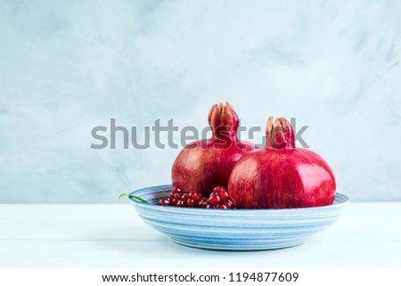 Pomegranate, three pieces, gray stone background, blue plate, southern fruit, copy place