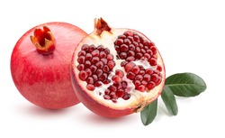 pomegranate with half of pomegranate and green leaves isolated on a white background