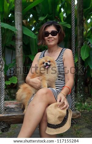 pomeranian dog sitting on woman leg
