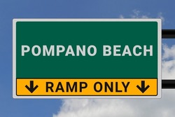 Pompano Beach logo. Pompano Beach lettering on a road sign. Signpost at entrance to Pompano Beach, USA. Green pointer in American style. Road sign in the United States of America. Sky in background