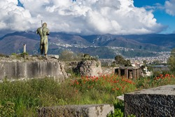 Pompeii ruins with red poppies in spring, Italy. On the left - the bronze sculpture by Igor Mitoraj - Daedalus, donated to Pompeii. In the distance-mountains and cloudy sky