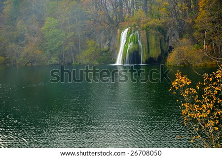 Pond and waterfall in autumn lush vegetation in Plitvice (Croatia - Hrvatska) with hazy and fairy atmosphere