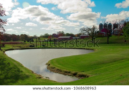 Pond in middle of large farm.