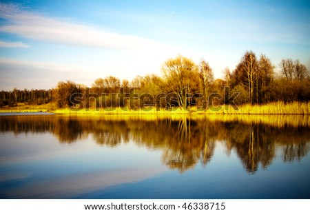 Pond water surface with reflection of colorful trees in autumn park