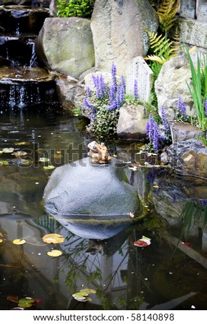 Pond with lotus leaves in the temple and frog statue