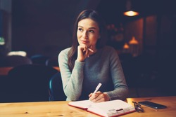 Pondering attractive young woman with pen in hand thinking on plans and writing list to do in notepad enjoying recreation time in stylish coworking space.Thoughtful student noting text information
