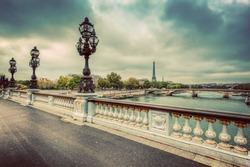 Pont Alexandre III bridge in Paris, France. Seine river and Eiffel Tower. Vintage