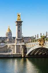 Pont Alexandre III bridge over river Seine and Hotel des Invalides in the background in the summer morning. Bridge decorated with ornate Art Nouveau lamps and sculptures. Paris, France