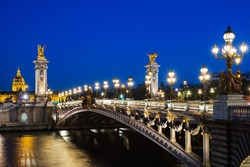 Pont Alexandre III bridge over river Seine and the Hotel des Invalides in the background in the summer evening. Beautiful night illumination of bridge. Paris, France
