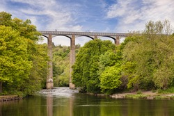 Pontcysyllte Aqueduct, built by Thomas Telford, and a World Heritage Site, reflecting in the River Dee, with people walking across, near Llangollen, County Borough of Wrexham, Wales, UK