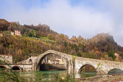 Ponte della Maddalena over the Cercchio River. Medieval bridge with magnificent architecture. Italy. Province of Tuscany. Outskirts of Bagni di Lucca
