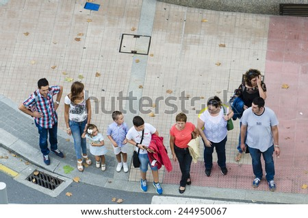 PONTEVEDRA, SPAIN - AUGUST 9, 2014: A group of people waiting time to cross the street at a crosswalk in the city.